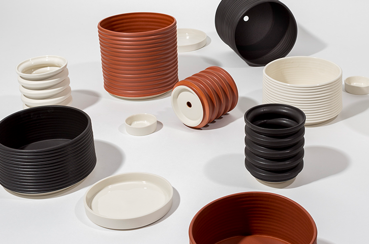 An assortment of ceramic planters and water trays by Andrew Molleur Ceramics