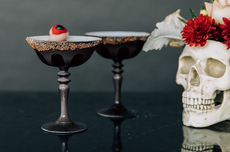 Two margaritas in grey coupe glasses with an orange salted rim, next to a skull vase filled with flowers