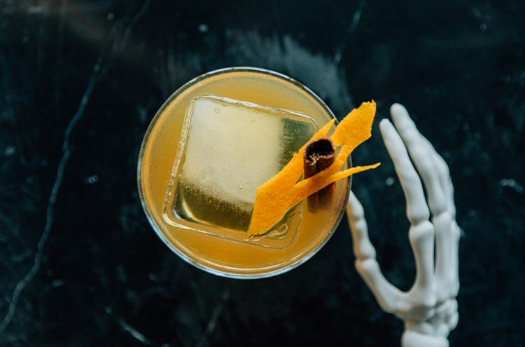 An old fashioned cocktail in a glass with a large ice cube and garnished with a cinnamon stick and orange peel, with a skeleton hand touching the glass
