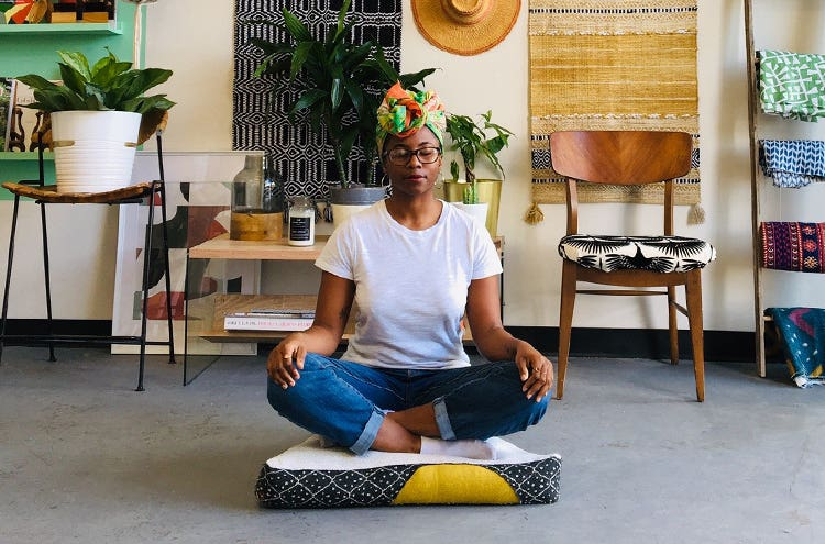 Nicole Crowder meditating in her studio while sitting on one of her handmade meditation pillows