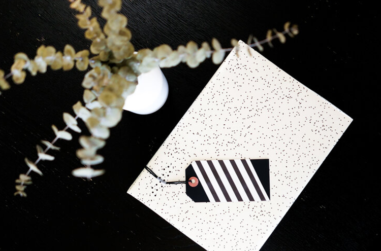 A gift wrapped in white and black spotted wrapping paper with a black and white tag and next to a vase of eucalyptus