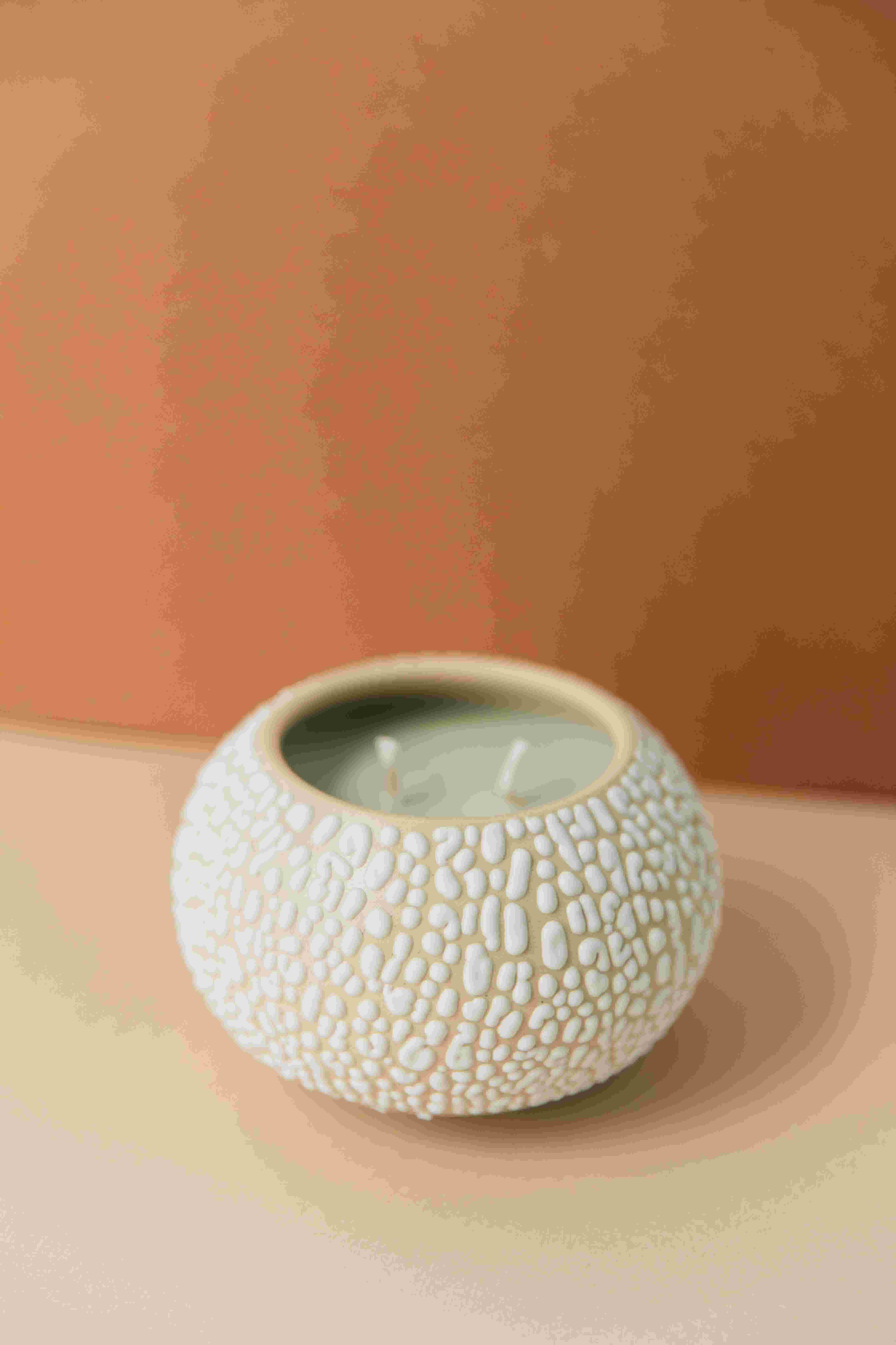Whitney Port x Favor's Teton candle, in a small globe-shaped container with a unique chunky white glaze