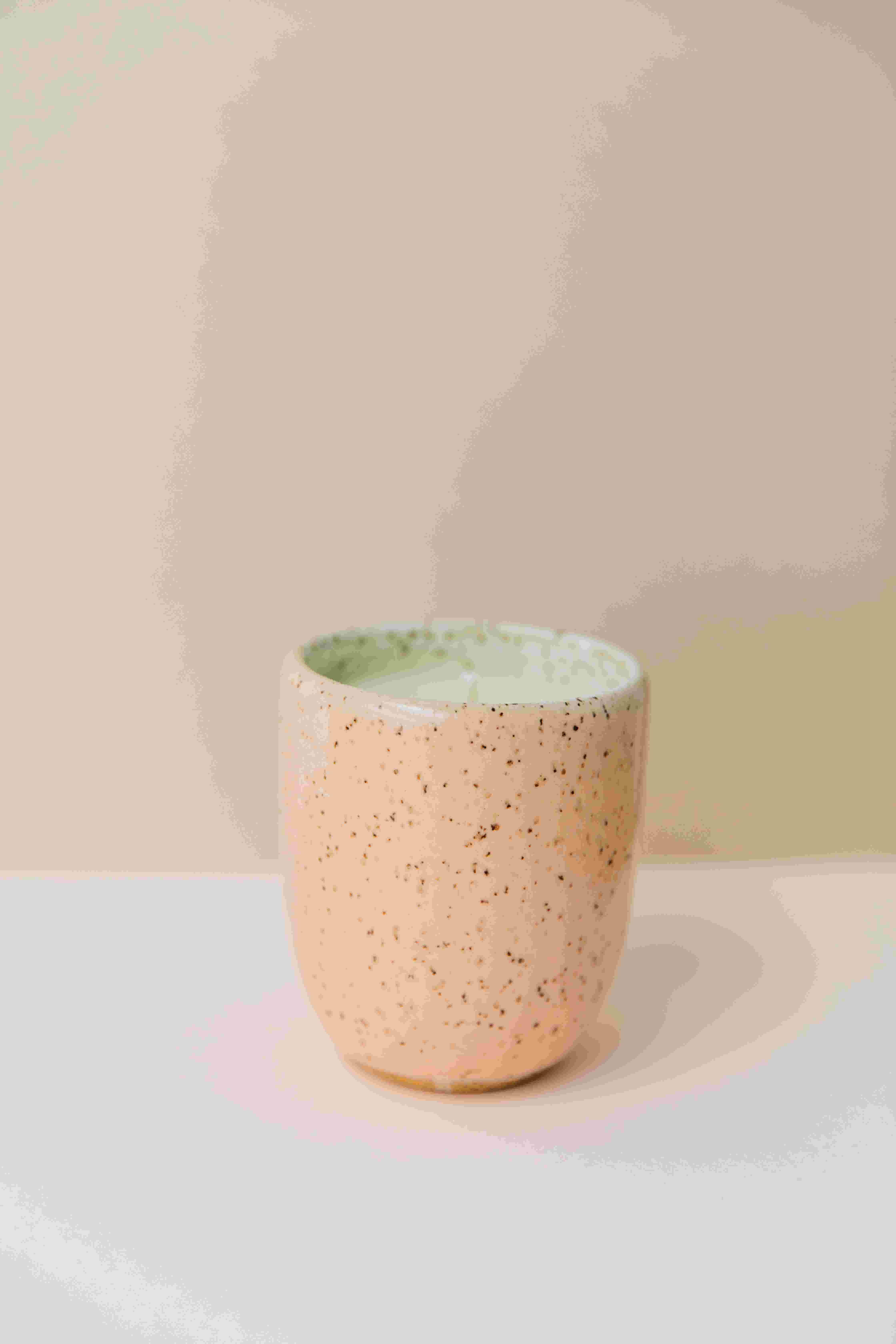 Whitney Port x Favor's Tahquitz candle in a glossy, speckled peach colored ceramic container