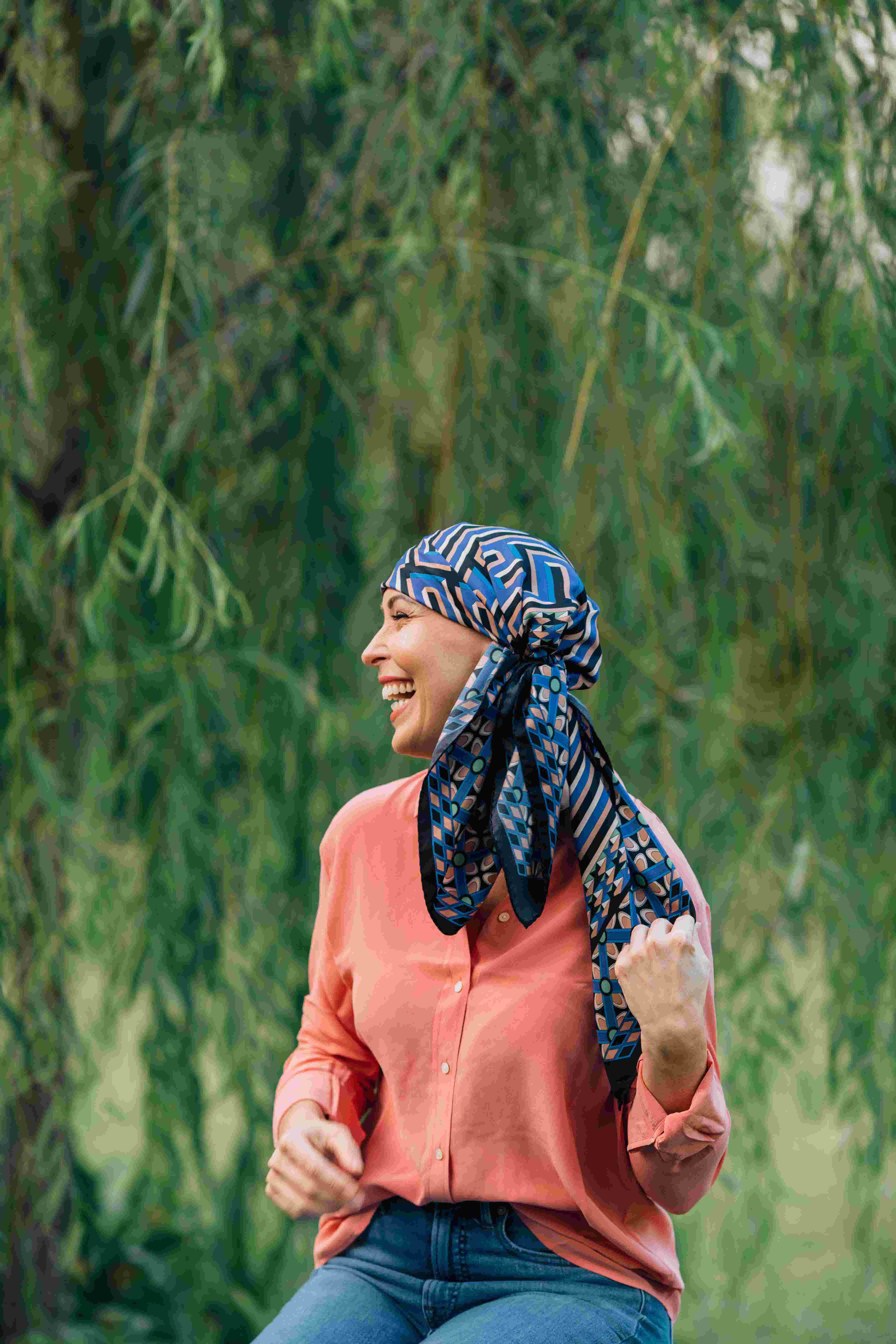 A woman in front of a tree wearing a silk scarf wrapped around her head