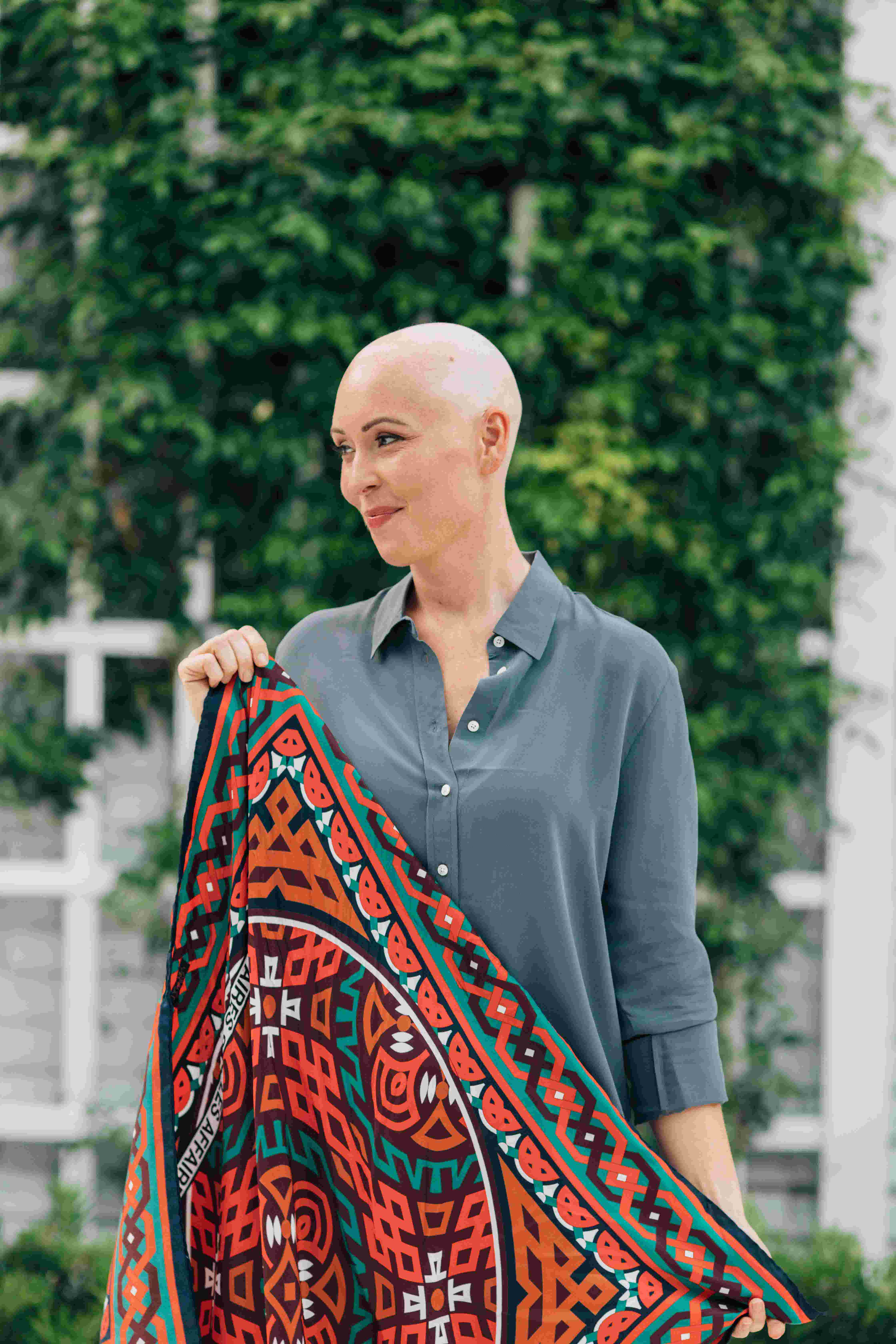 A woman with no hair smiling and holding a silk scarf in her hands