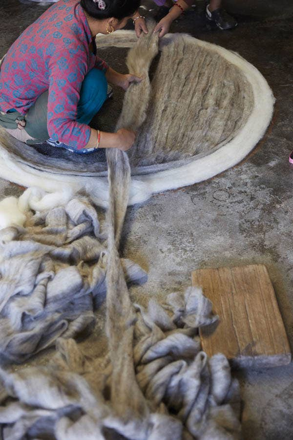 A female artisan working with strips of gray felted wool to make a round rug