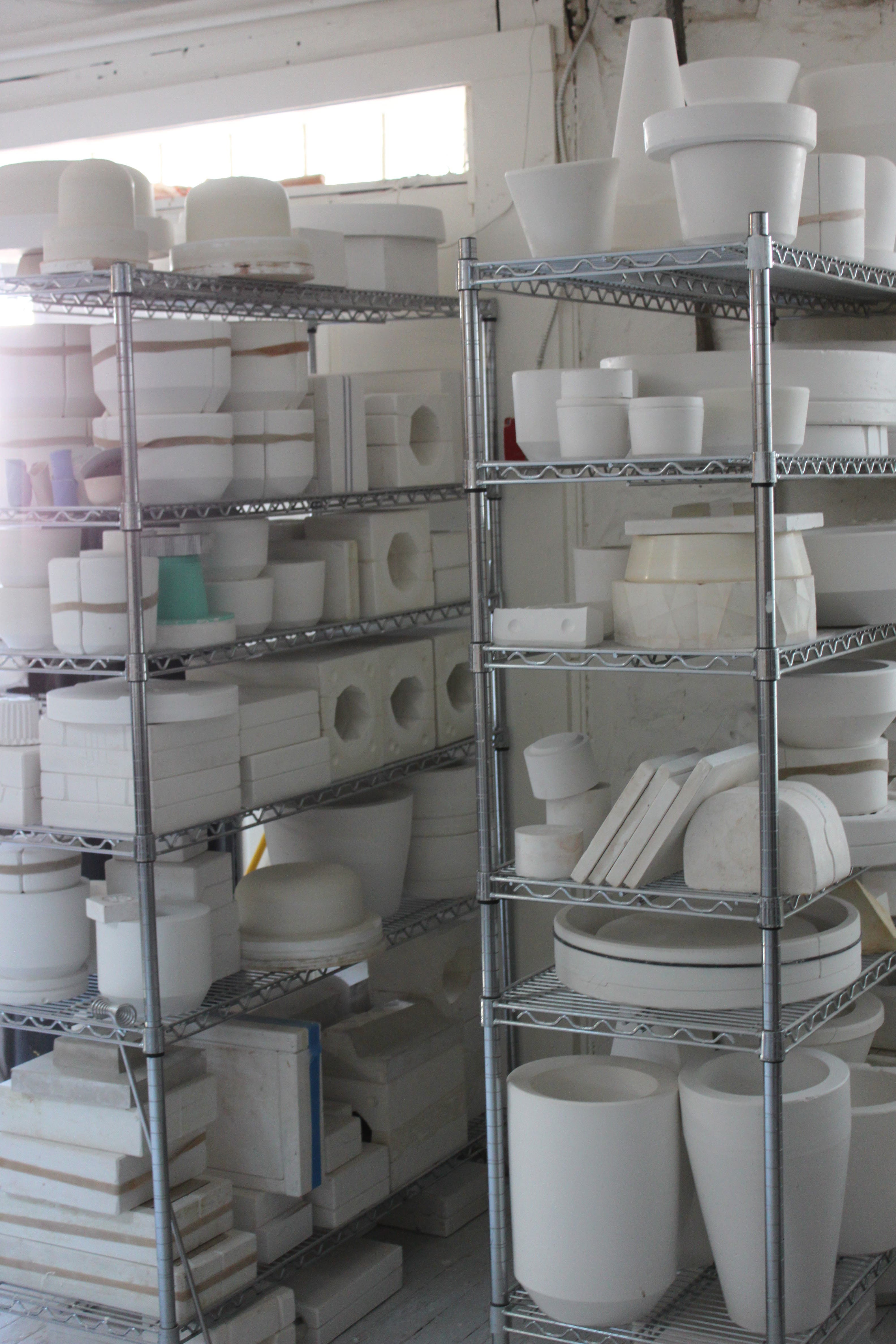 A shelf of in-progress white ceramic pieces by Andrew Molleur