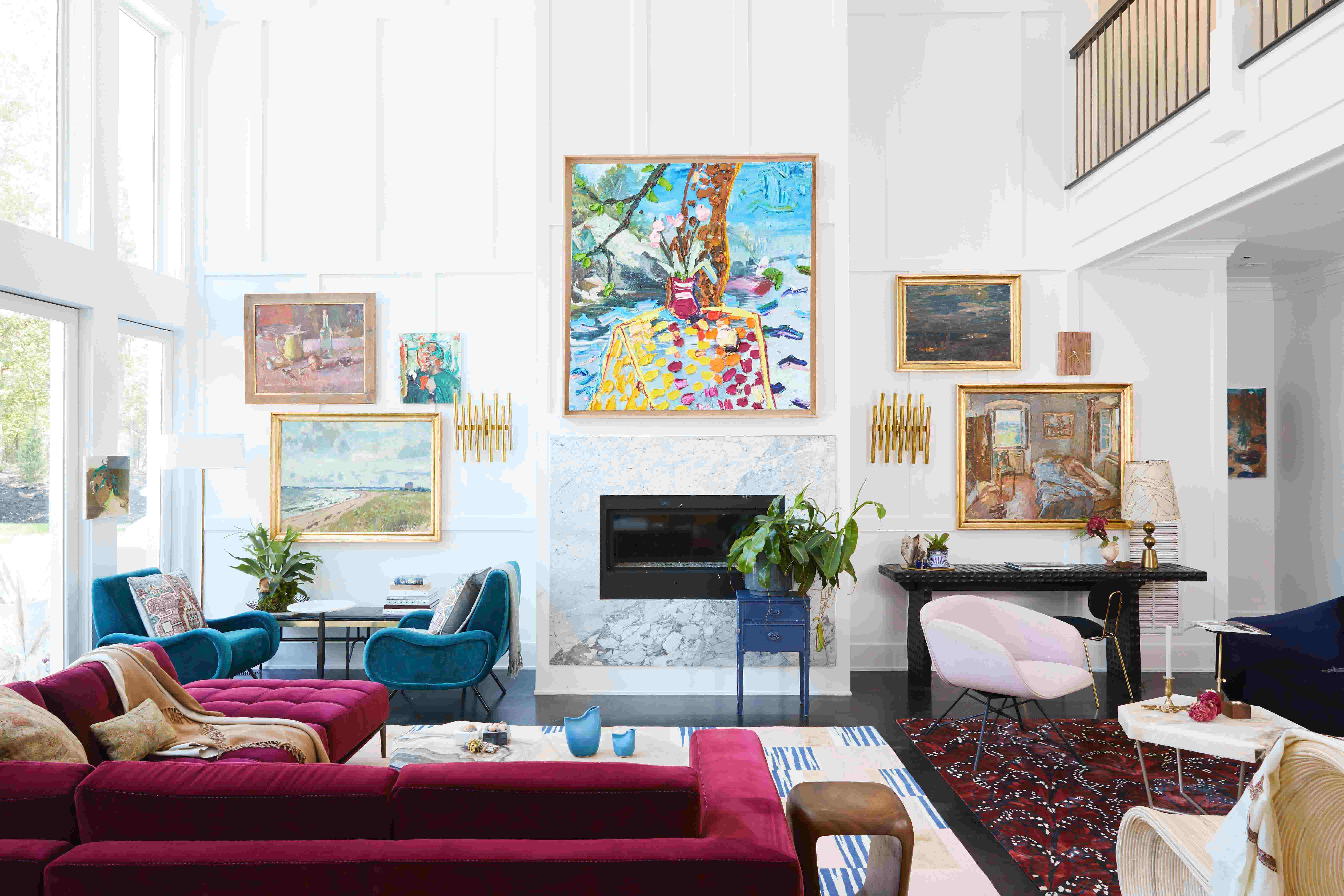 A neutral living room with pops of color throughout including velvet furniture and various pieces of art