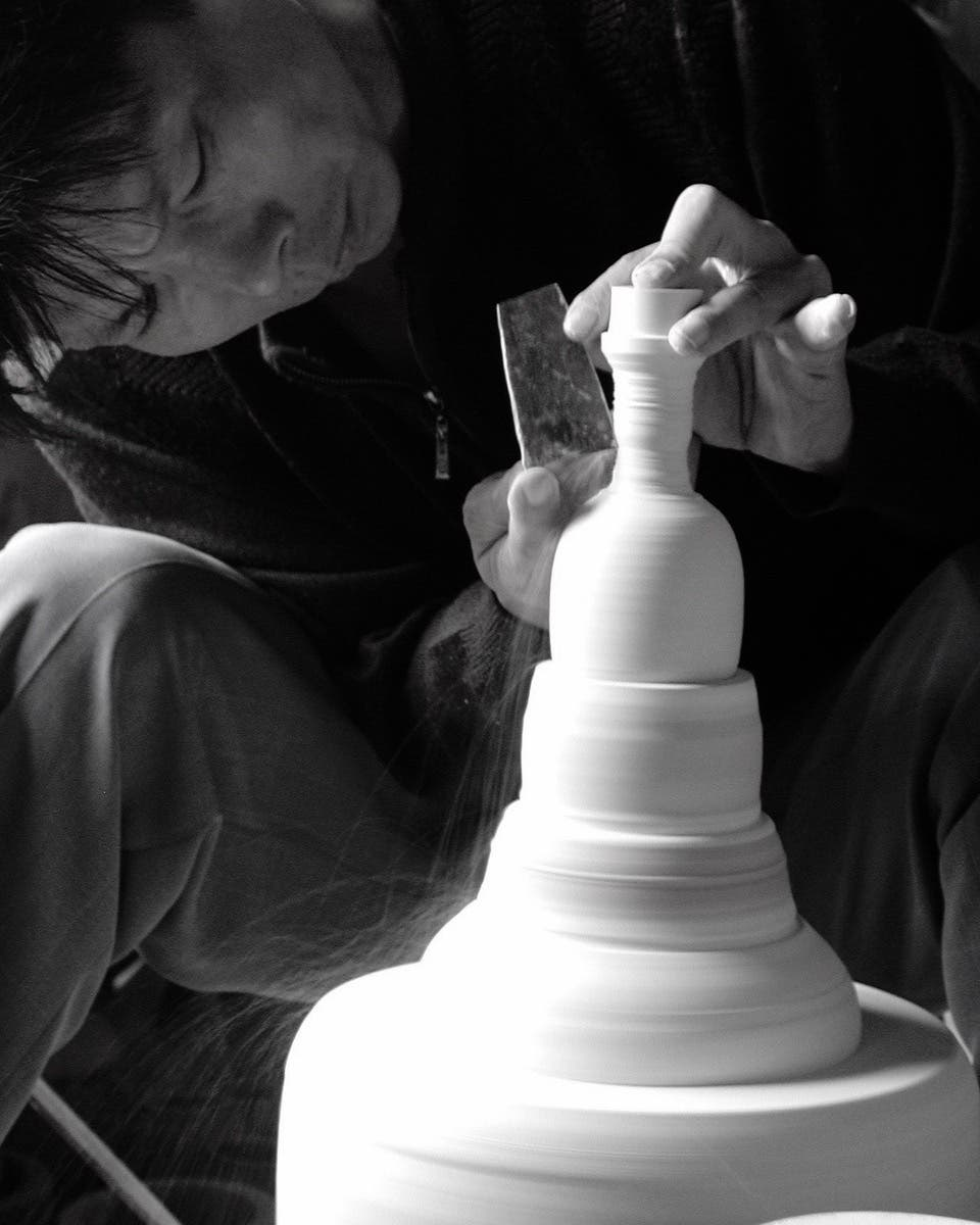 An artisan at Middle Kingdom hand-making a porcelain vase on a pottery wheel