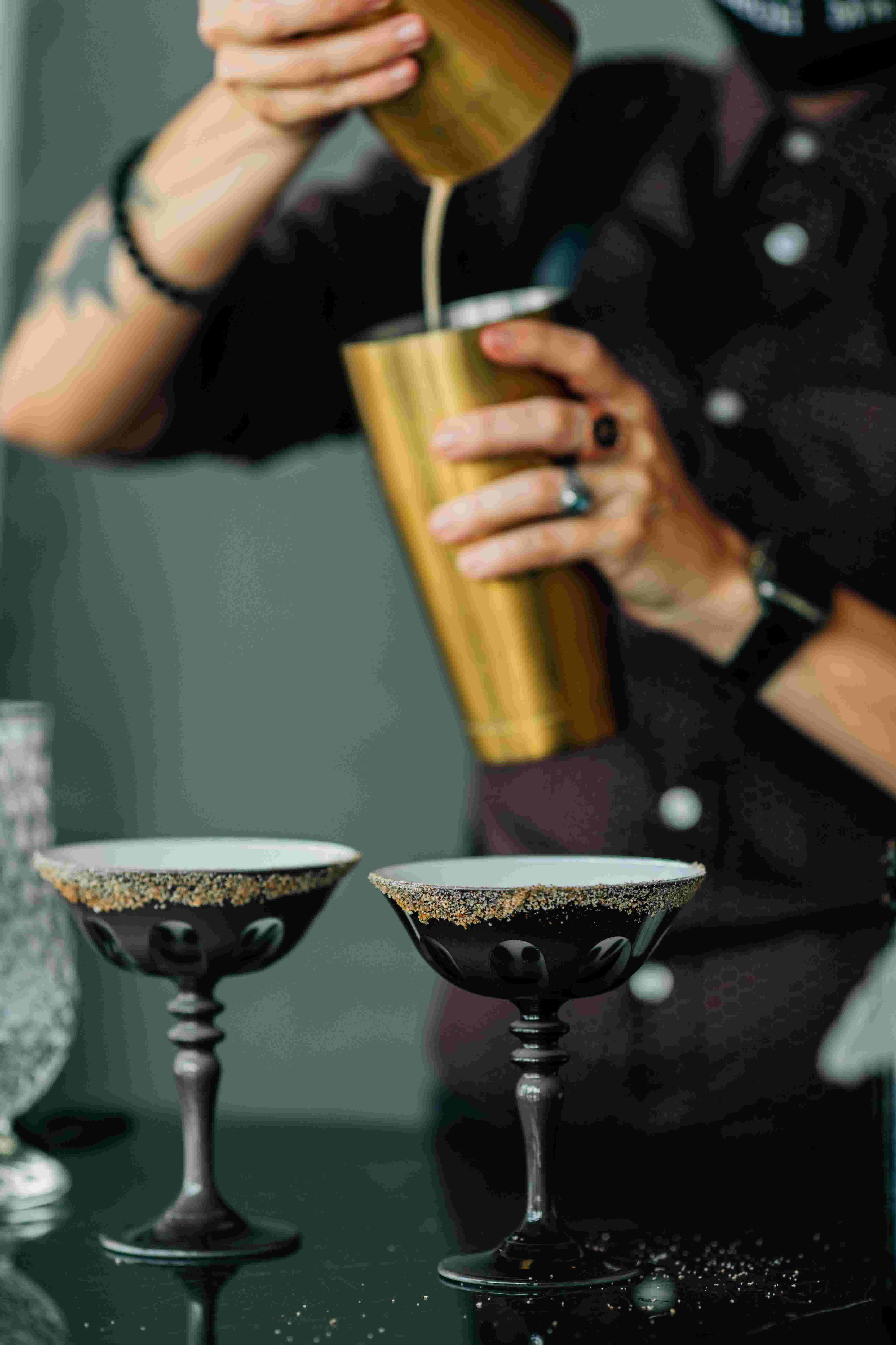A bartender mixing up a cocktail and pouring between two gold colored mixing shaker cups
