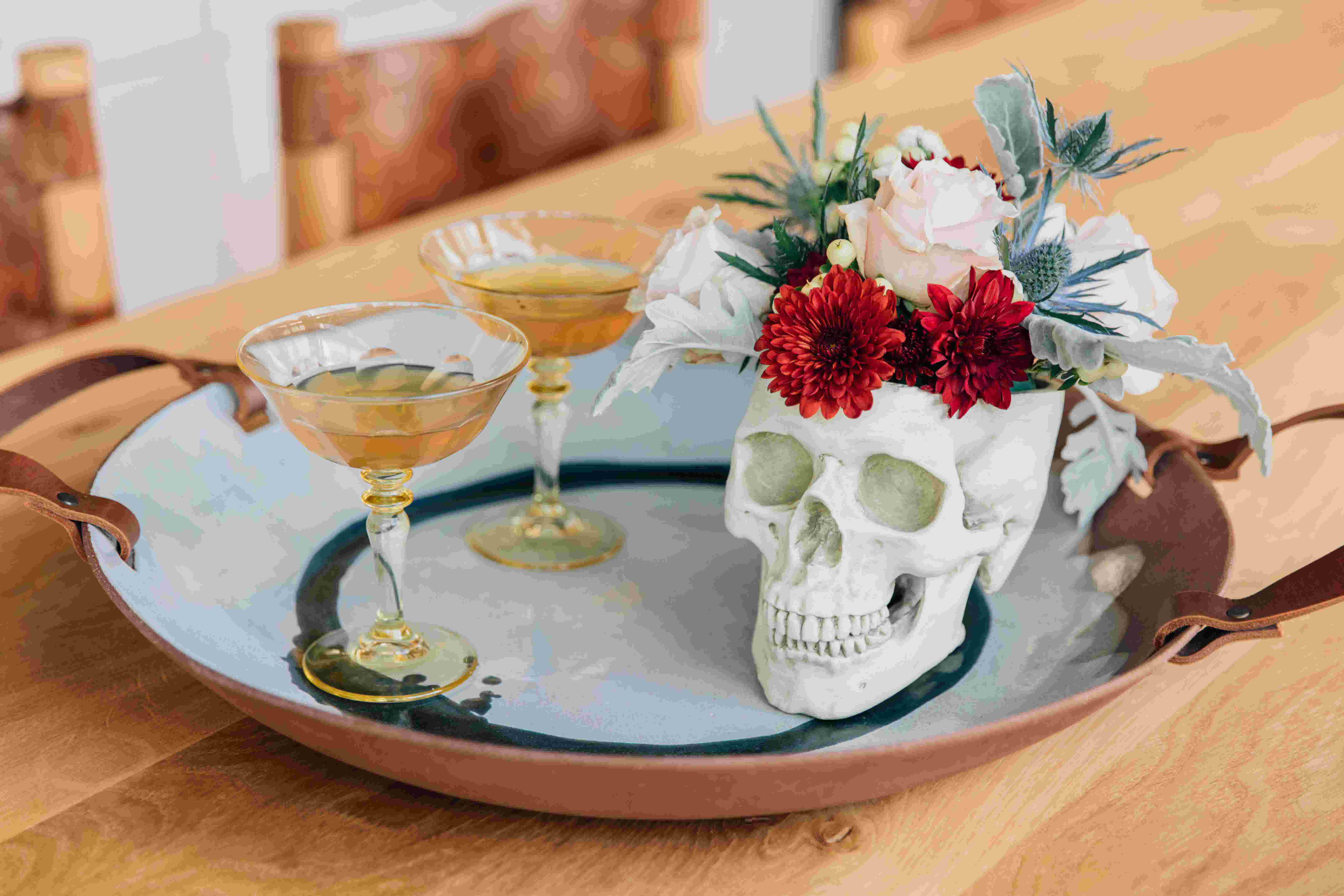 A pair of margaritas in yellow Rialto glasses from Favor on a ceramic tray next to a skull decoration filled with flowers