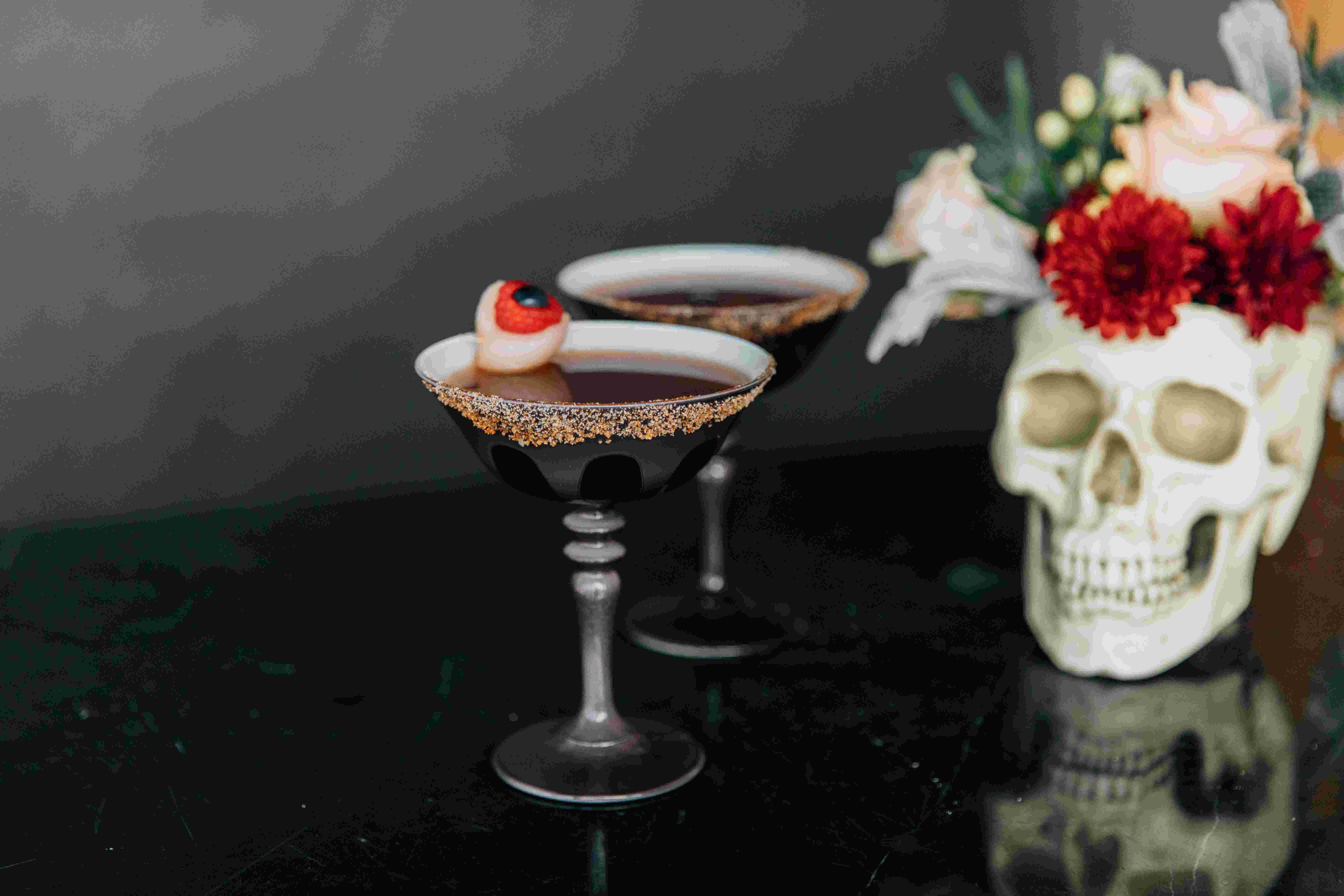 Two margaritas in grey coupe glasses, one with a fake eyeball candy garnish, in front of a skull decoration filled with flowers