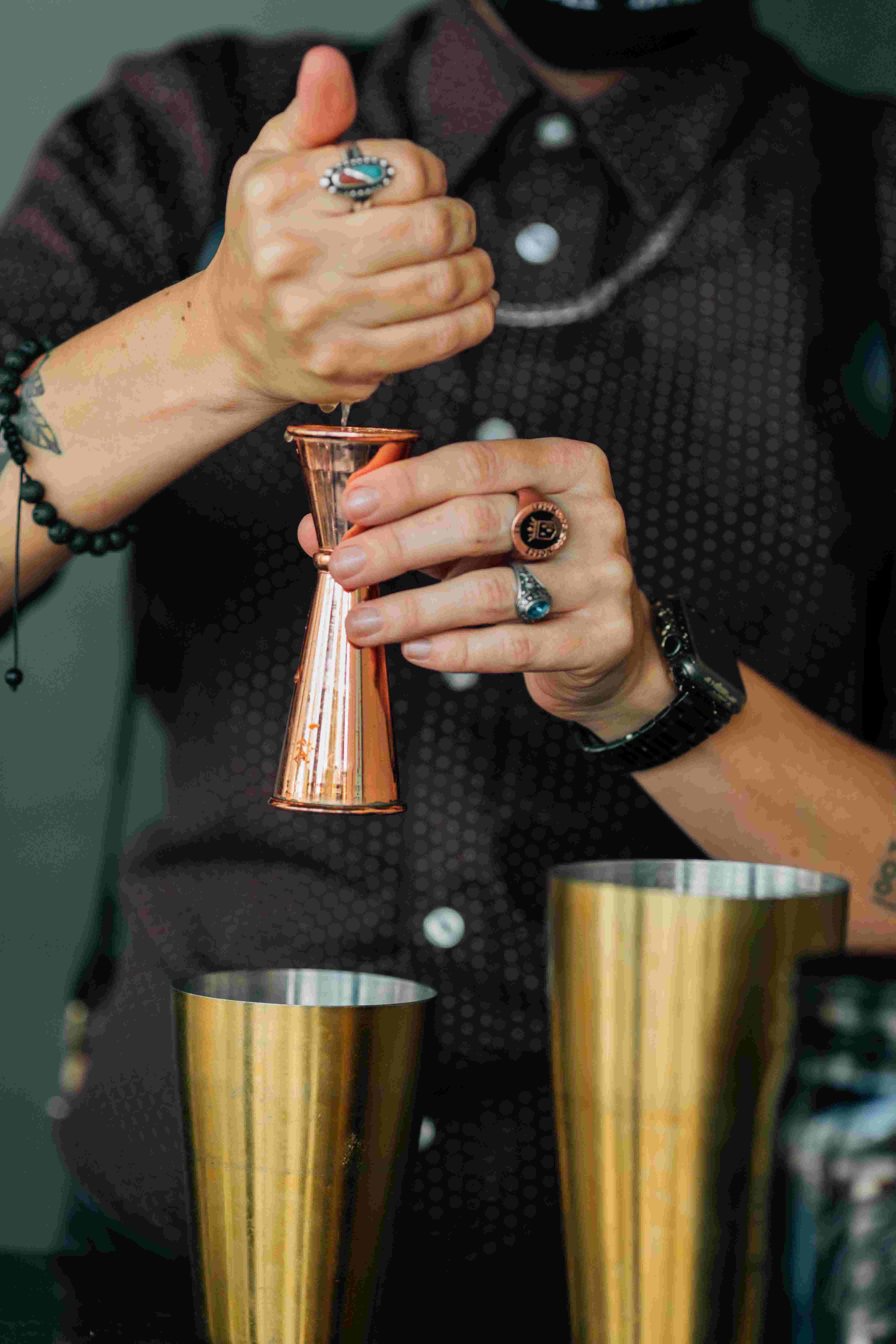 A bartender working with copper and gold-colored barware equipment to make a cocktail