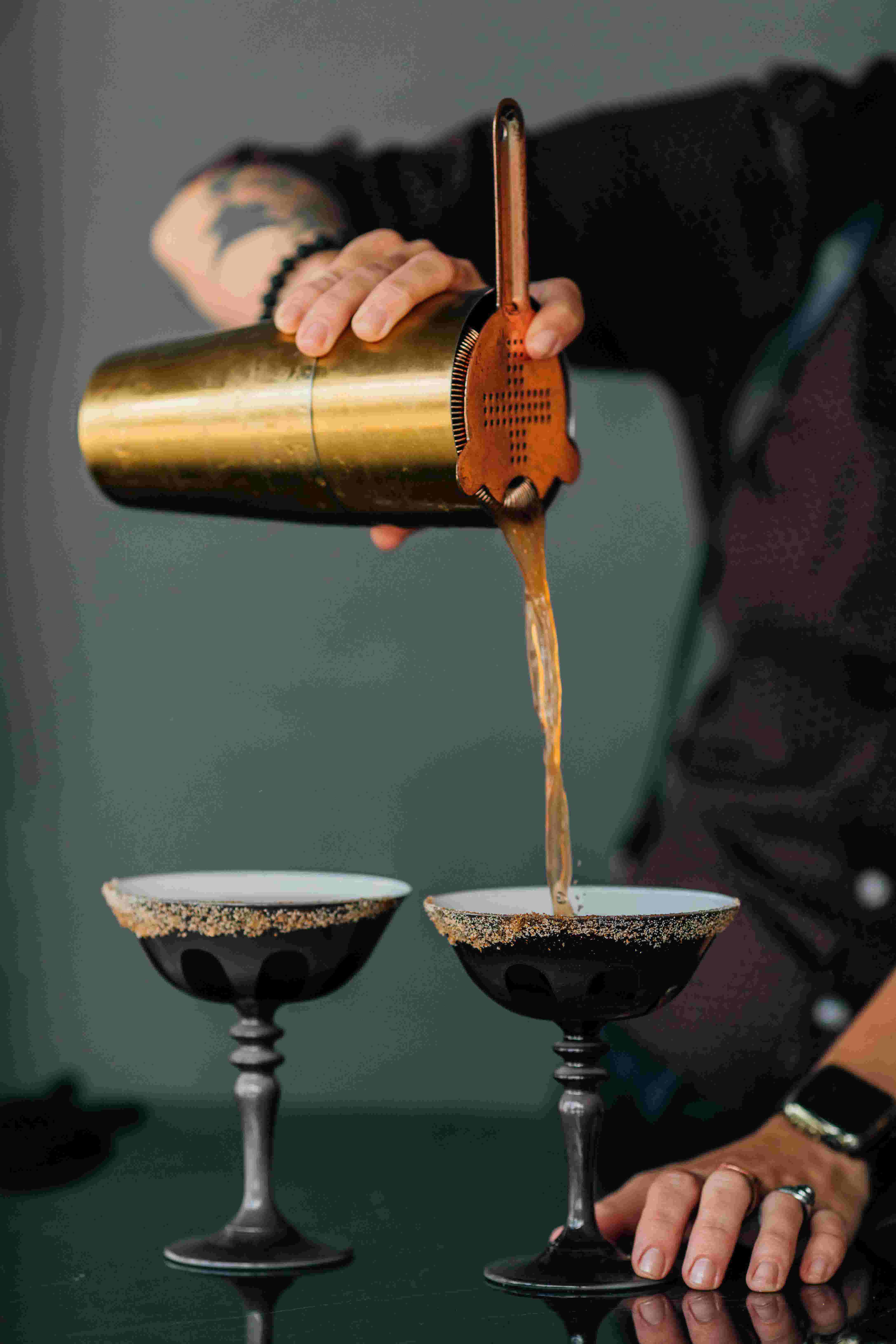 A bartender pouring a cocktail into two grey Rialto glasses from Favor using a gold mixing cup and copper strainer tool