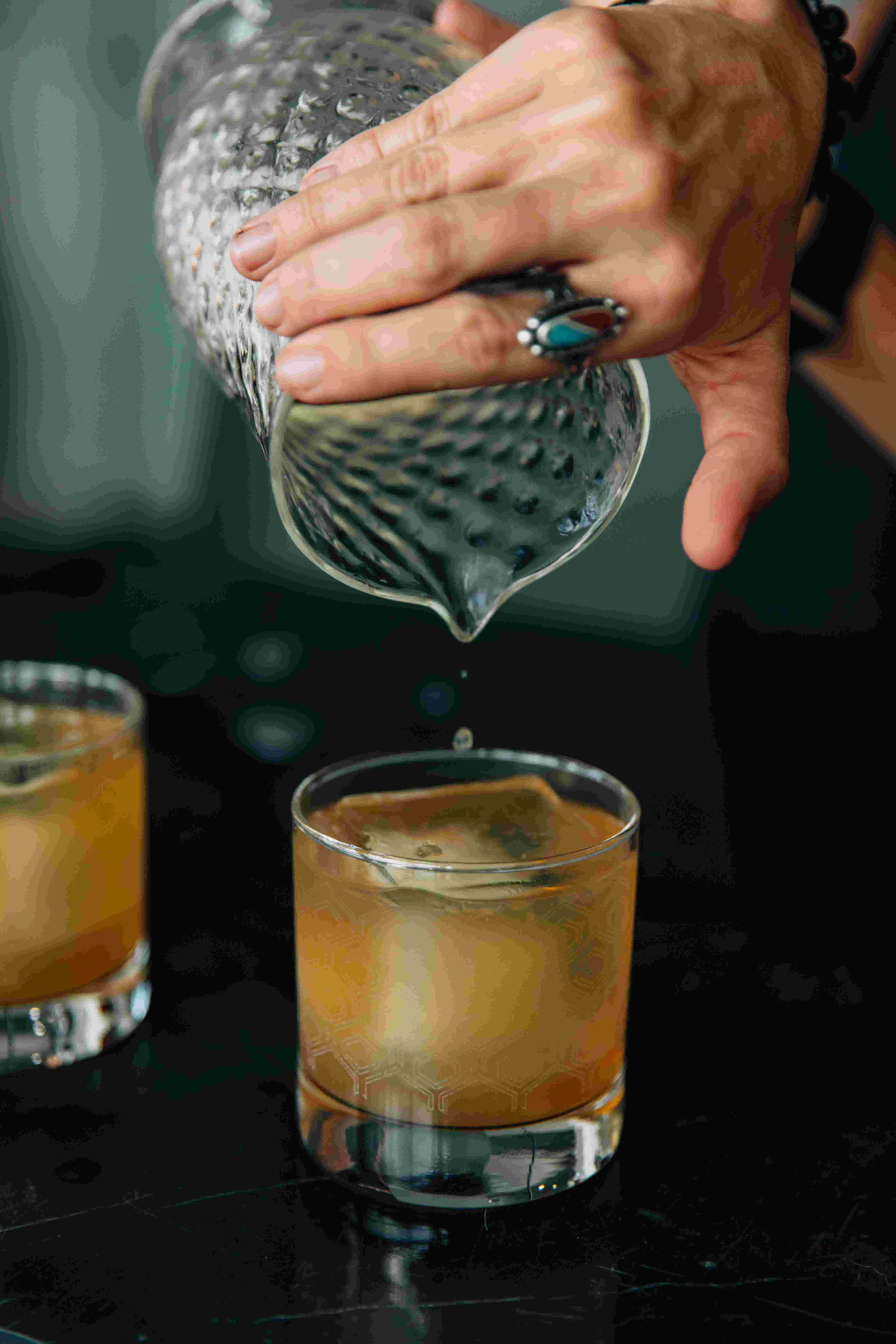 A bartender pouring a cocktail from a clear pitcher into a clear etched lowball glass