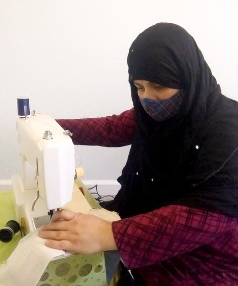 Woman sewing face masks for Stitch Buffalo x Favor