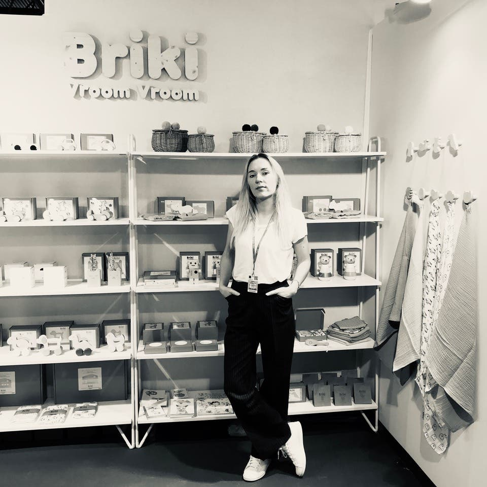 Founder of Briki Vroom Vroom in front of display shelf of wooden toys