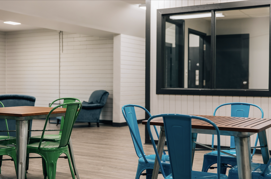 Green and blue dining chairs with lounge chair in the background at the Youth Crisis Center House of Hope