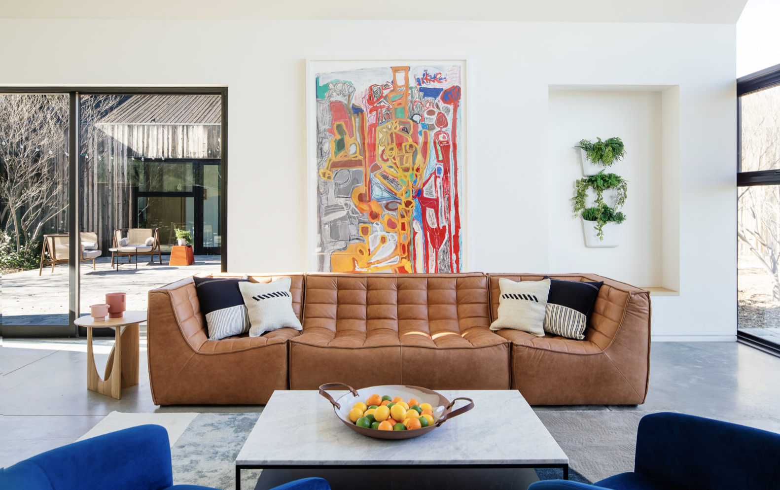 A brown leather sofa iin front of a colorful large piece of artwork