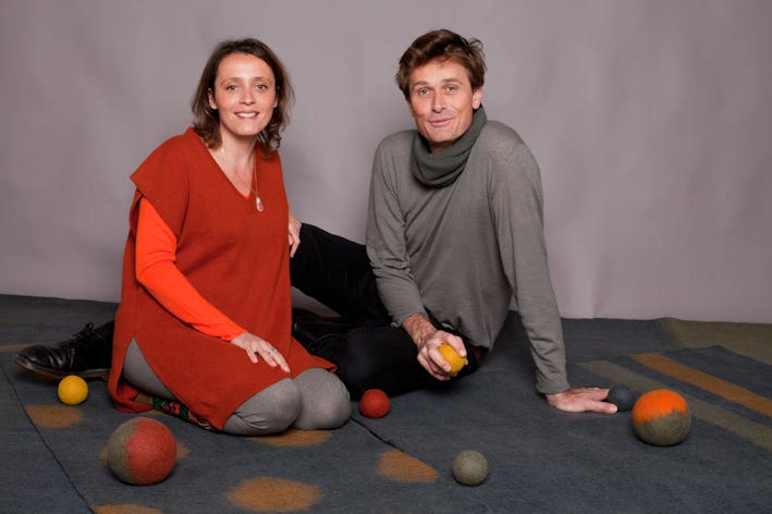 The owners of MUSKHANE sittinig on the ground surrounded by felt balls
