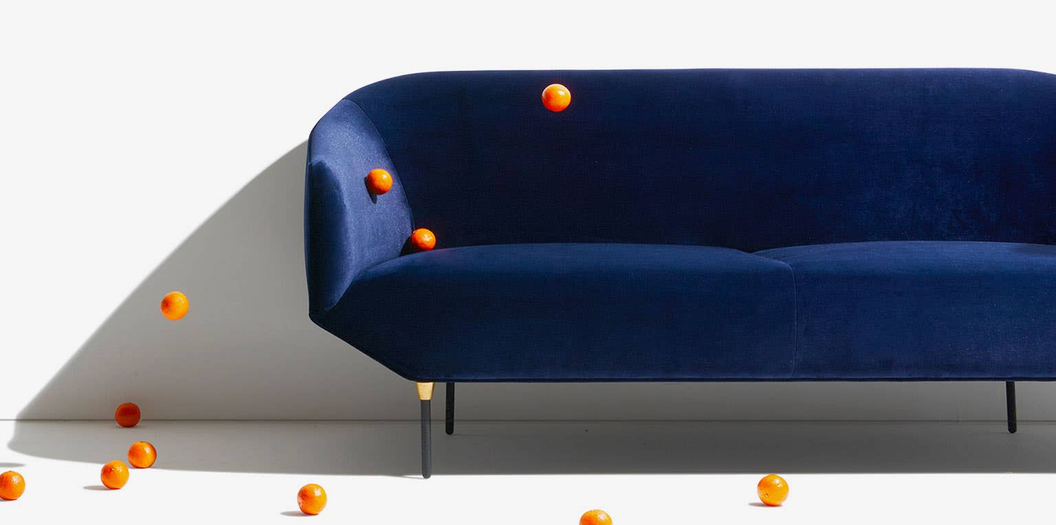 A blue Bale Sofa from Inndustry West surrounded by oranges