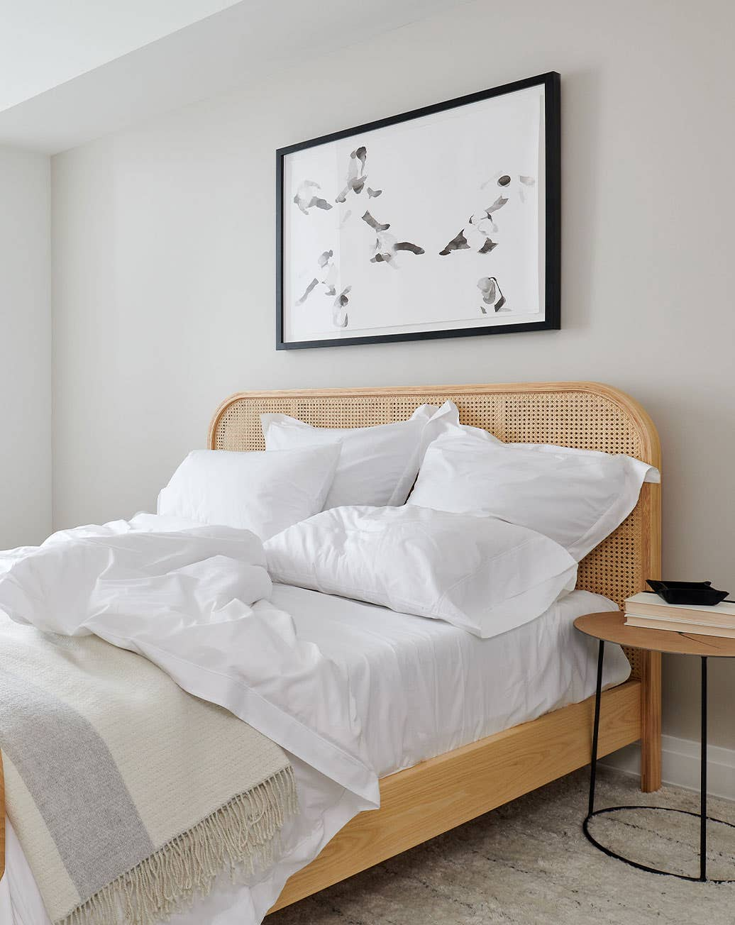A bedroom furnished with Industry West furinture including a cane bed and wooden side table