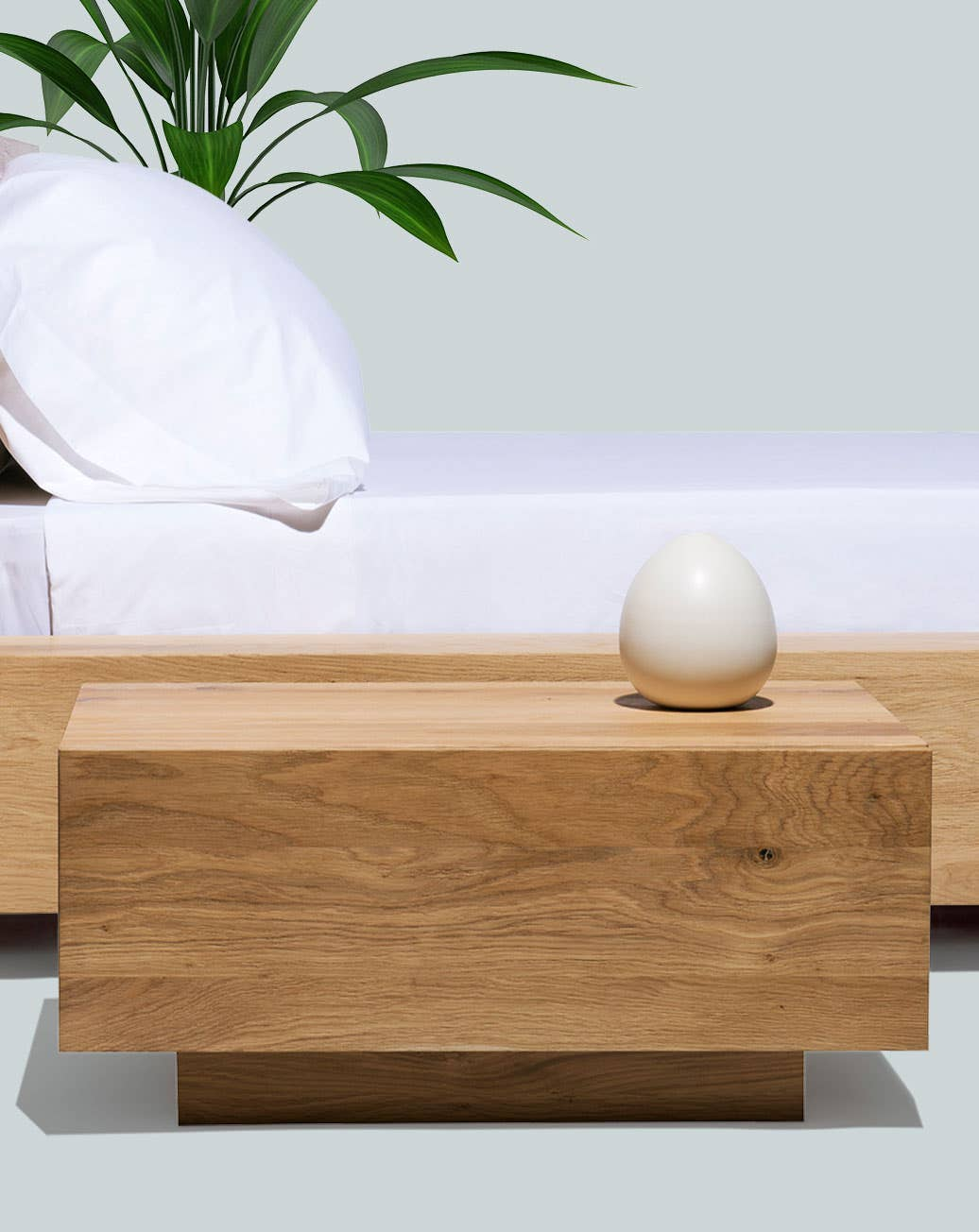 The Industry West Madra nightstand in front of a bed with a plant in the background.