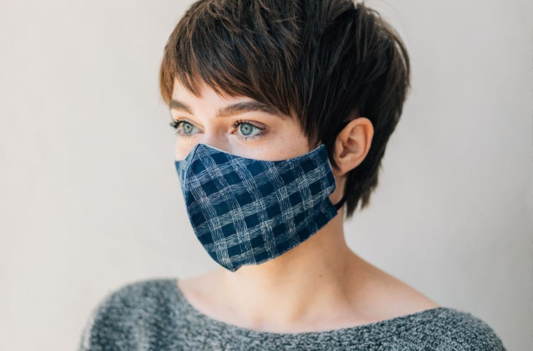 A girl with brown hair wearing a blue plaid mask made by Stitch Buffalo