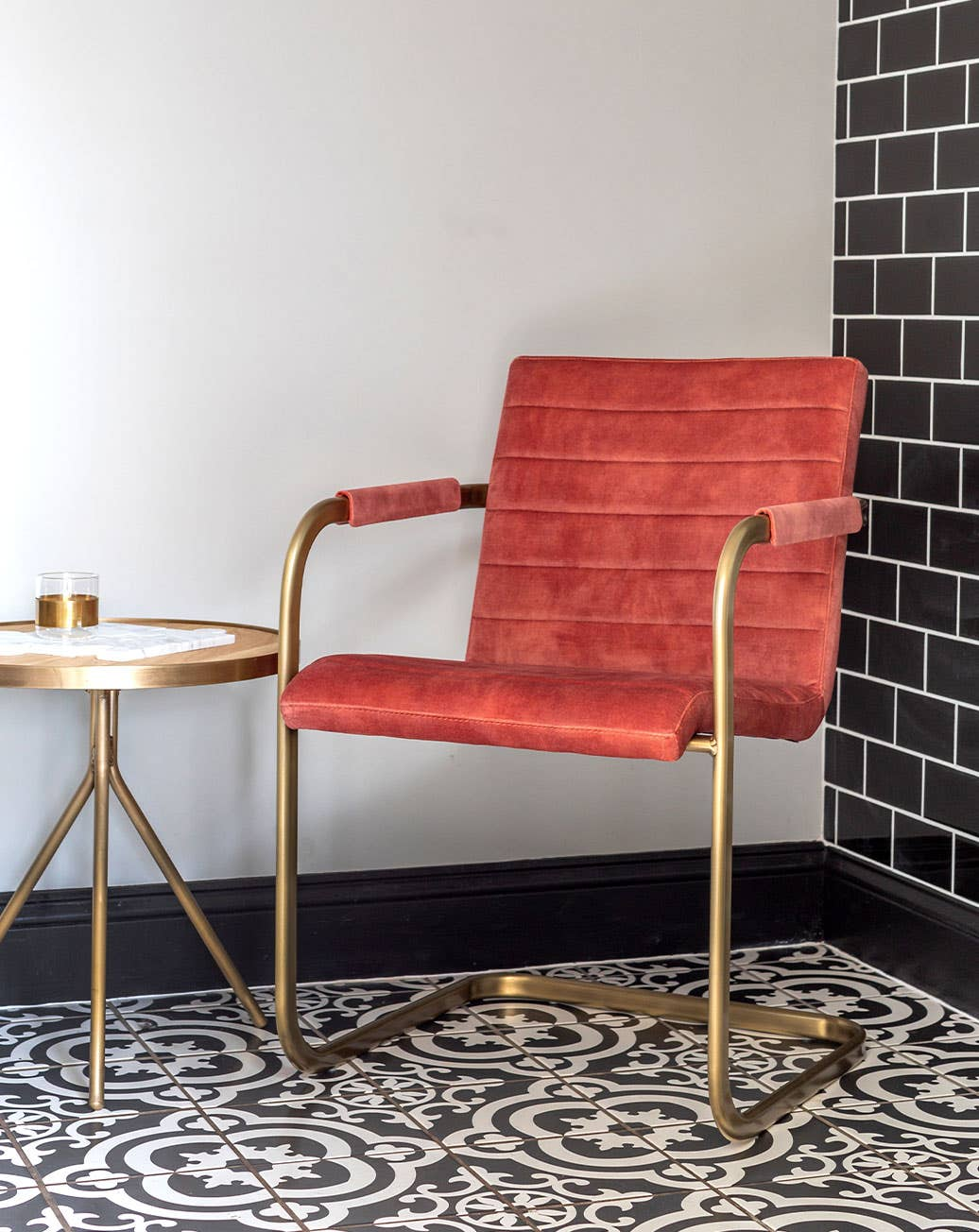Industry West Sable Armchair in blush with brass frame in a room with black and white tile
