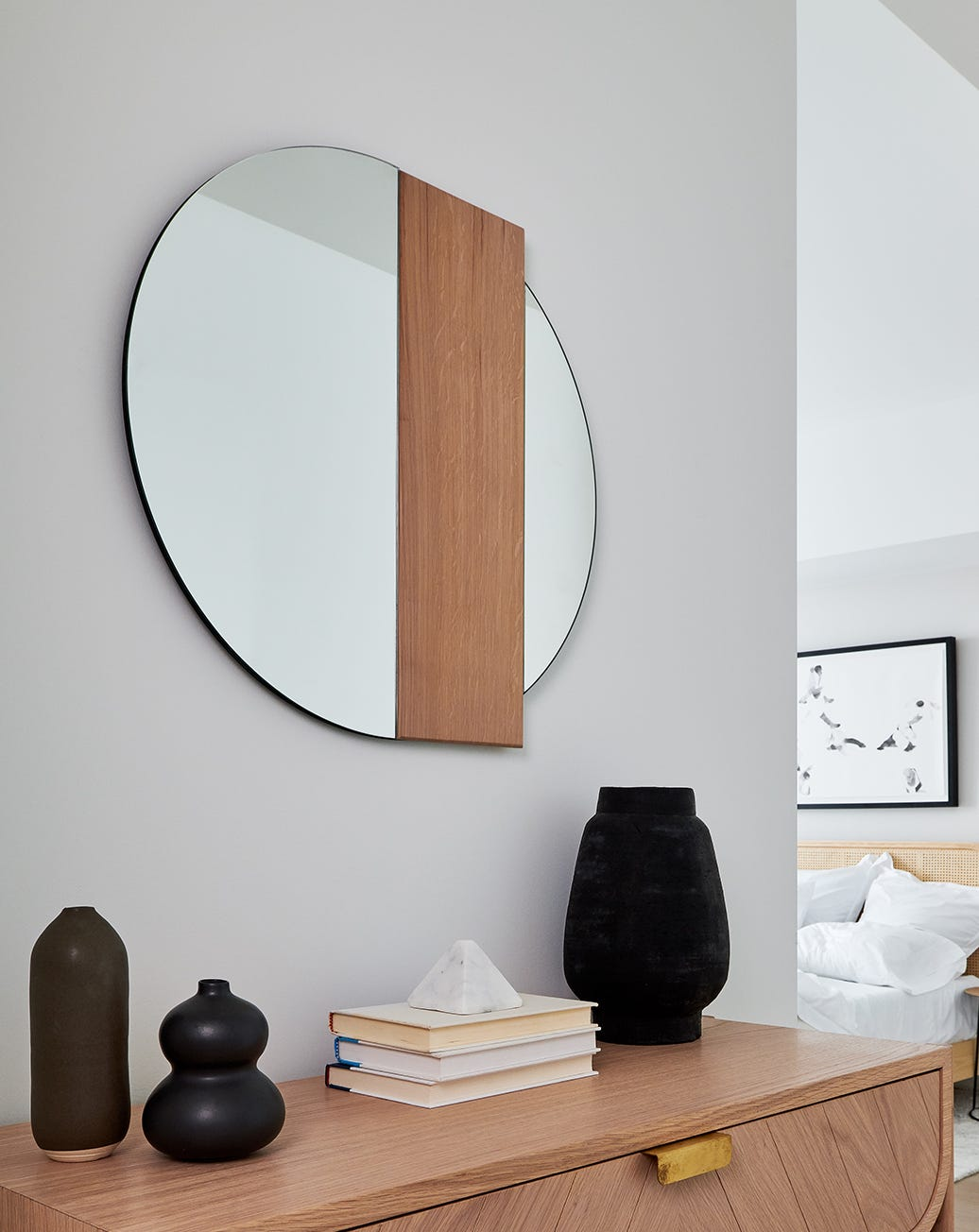 A round mirror with a rectangular wooden accent hanging over a wooden console table