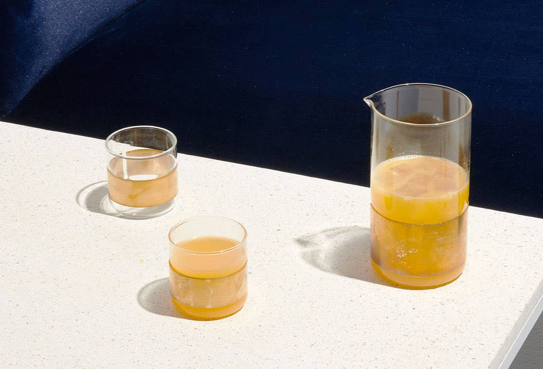 Two glass cups and a glass pitcher on a white terrazzo tabletop