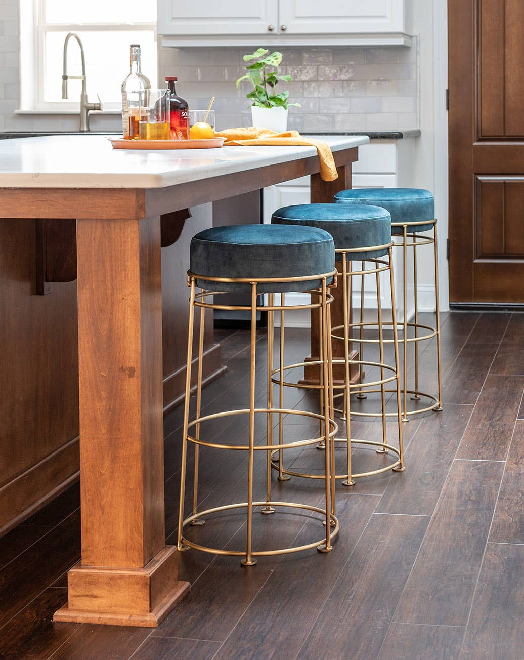 Three brass Rosa Bar Stools upholstered in blue velvet at a kitchen island