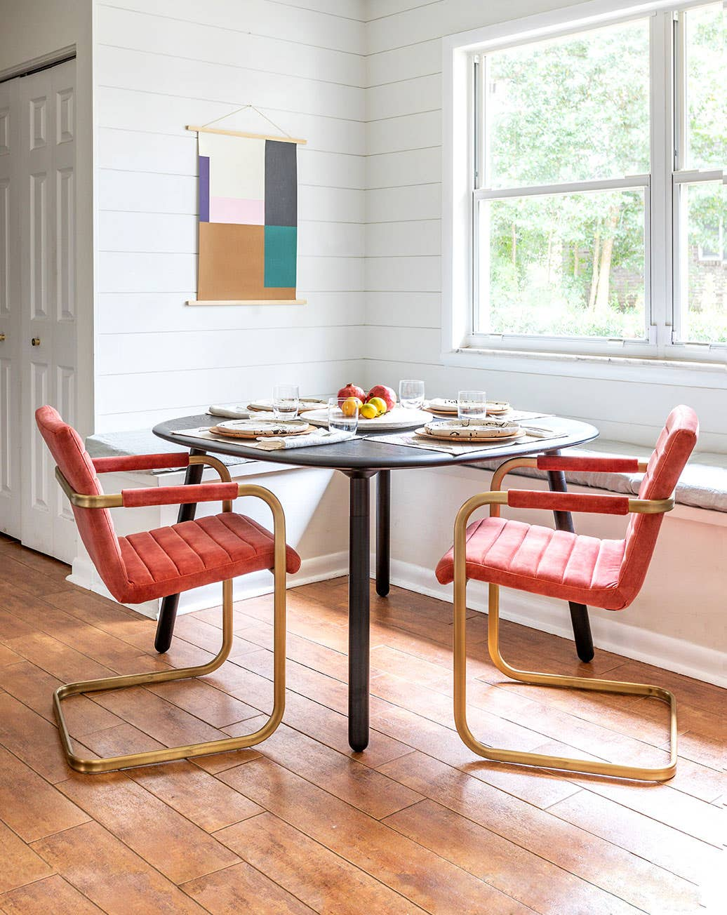 Two Sable Armchairs with brass frame and blush velvet upholstery at a breakfast table