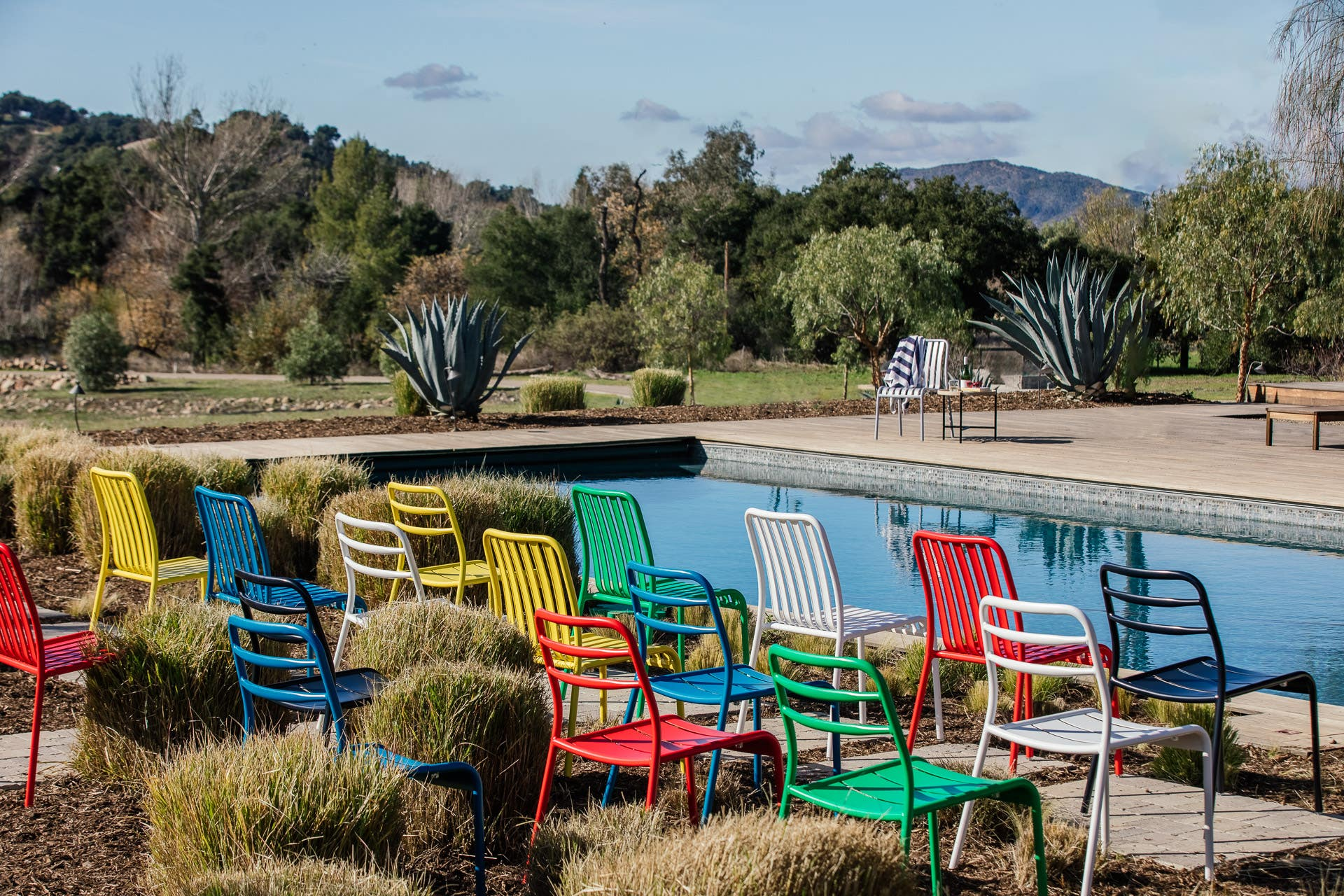 Industry West outdoor chairs in red, green, blue, yellow, and white by a pool in Ojai, California