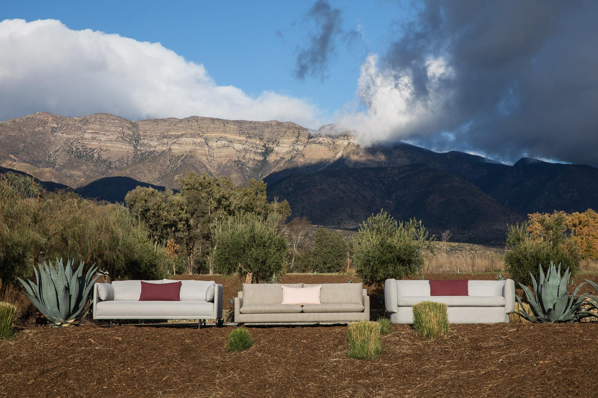 Three Industry West sofas with mountains and clouds in the background