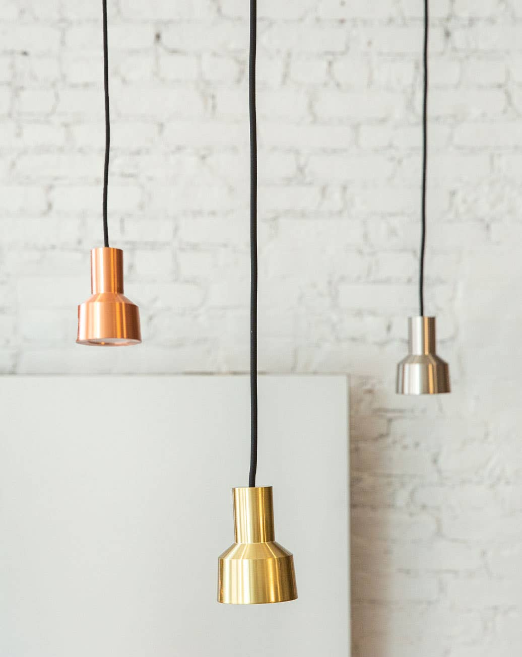 Three Fauve pendant light fixtures from Industry West, in copper, brass, and silver