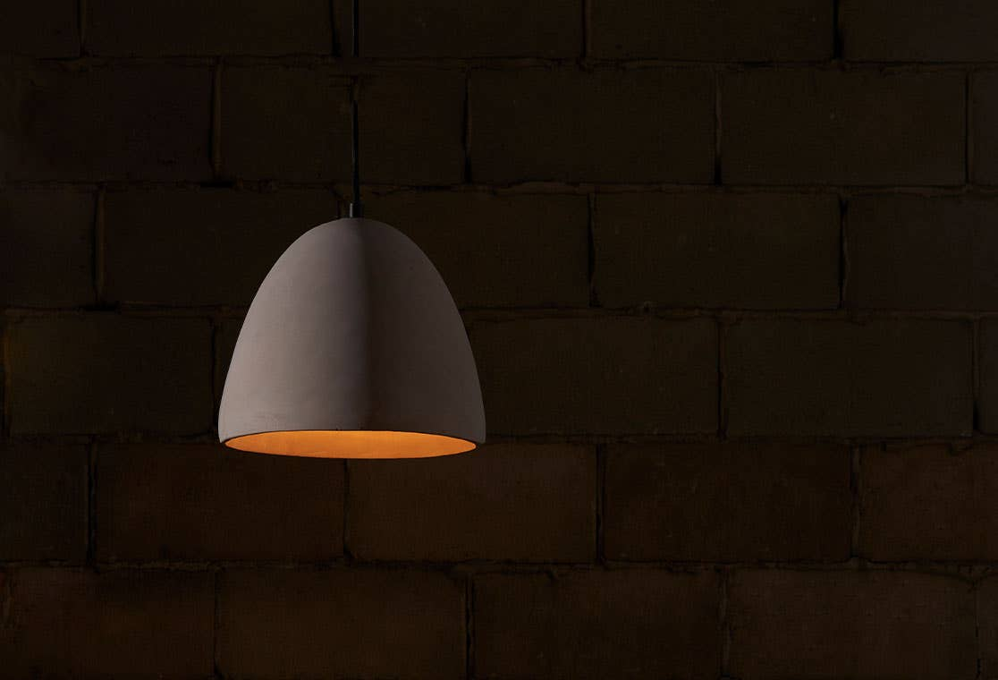 Industry West Alexander pendant lamp, illuminated against a dark background