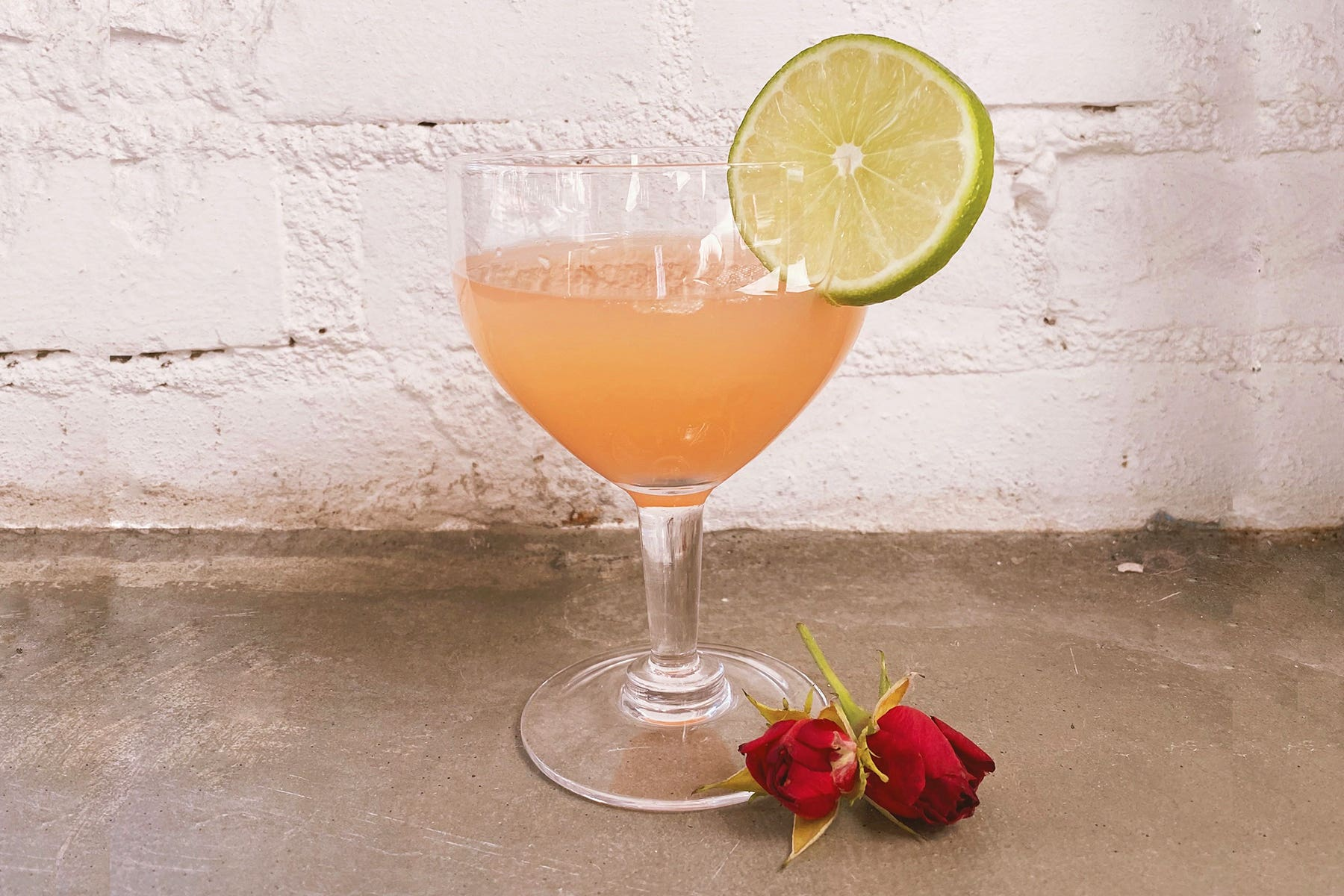 A pink mocktail in a wine glass garnished with a lime and small roses