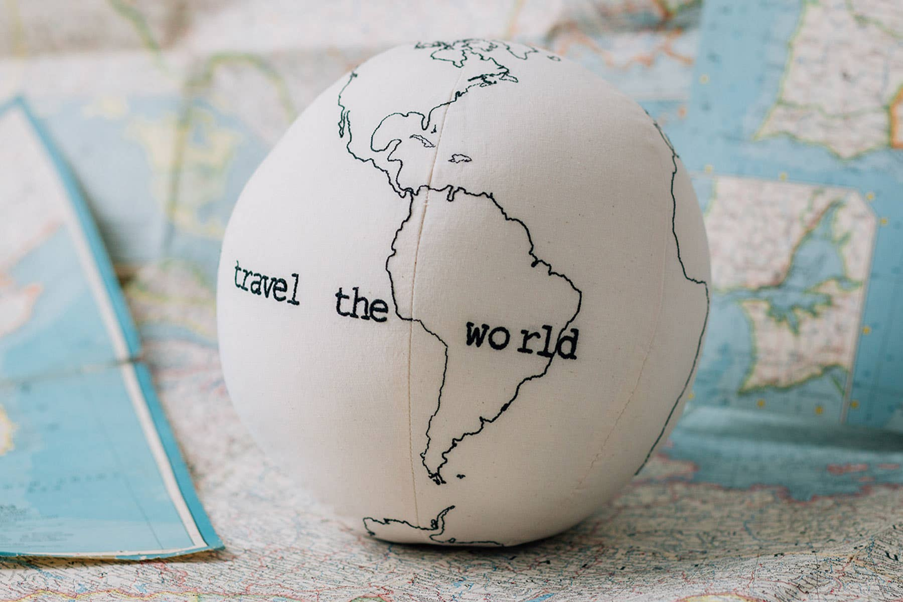 "A stuffed globe kid's toy that says ""travel the world"""
