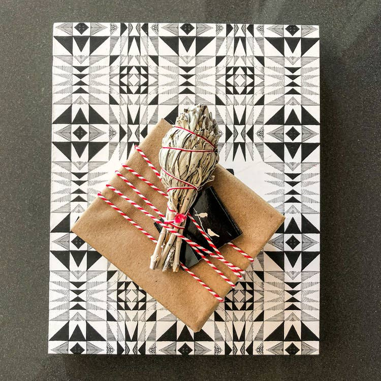 A creatively wrapped present with black and white patterned wrapping paper with a smaller brown box on top and sage. a