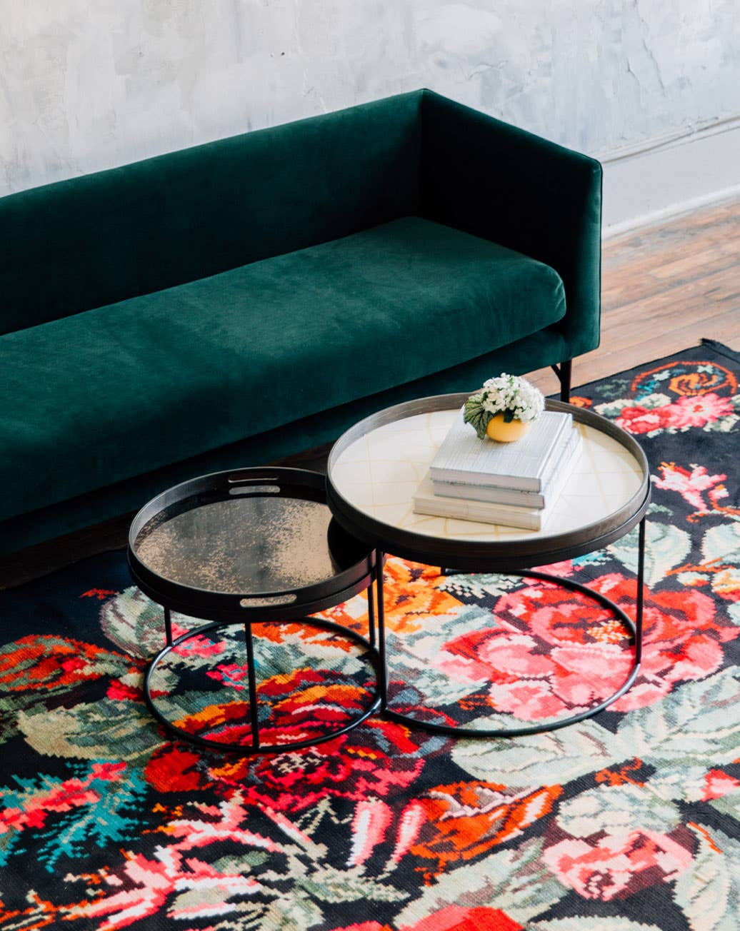 A green velvet Dune sofa from Industry West on a vintage floral rug with round coffee tables