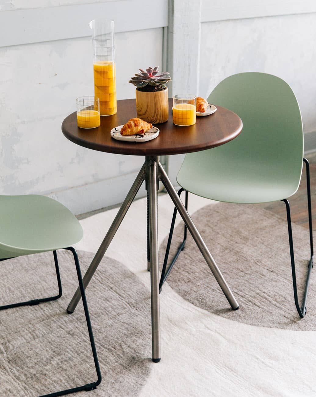 Two matcha green Bell chairs from Industry West at a small breakfast table