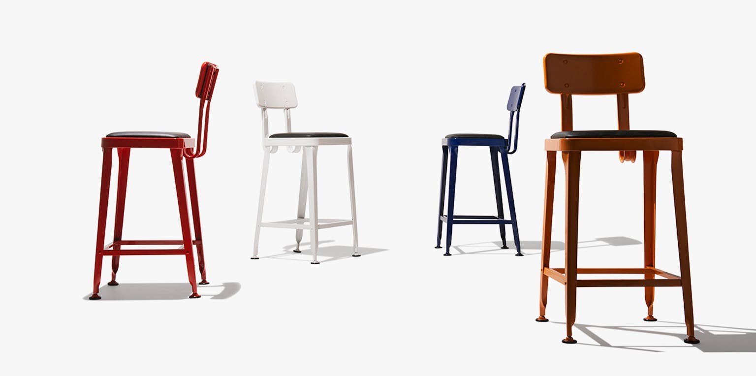 Four Industry West Octane stools facing different directions in red, white, blue, and orange