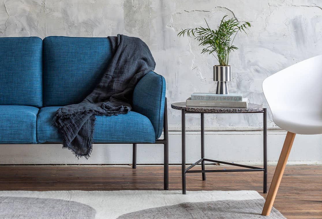 Industry West Terrazzo Side Table in a living space next to a blue Hew sofa