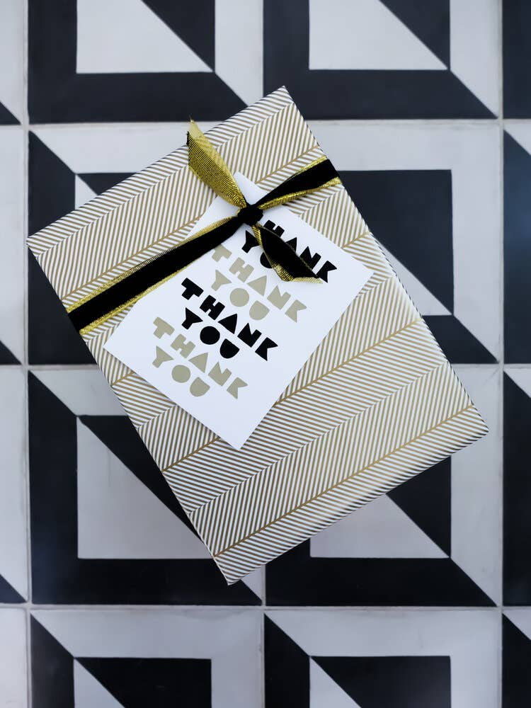A gold and white wrapped present with a thank you card and tied with black and gold ribbons