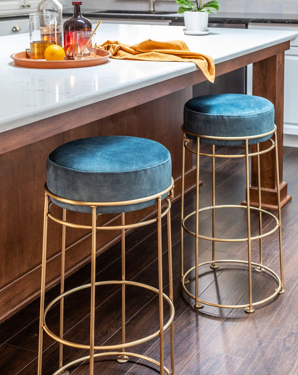 Three Industry West Bell bar stools in black at a countertop